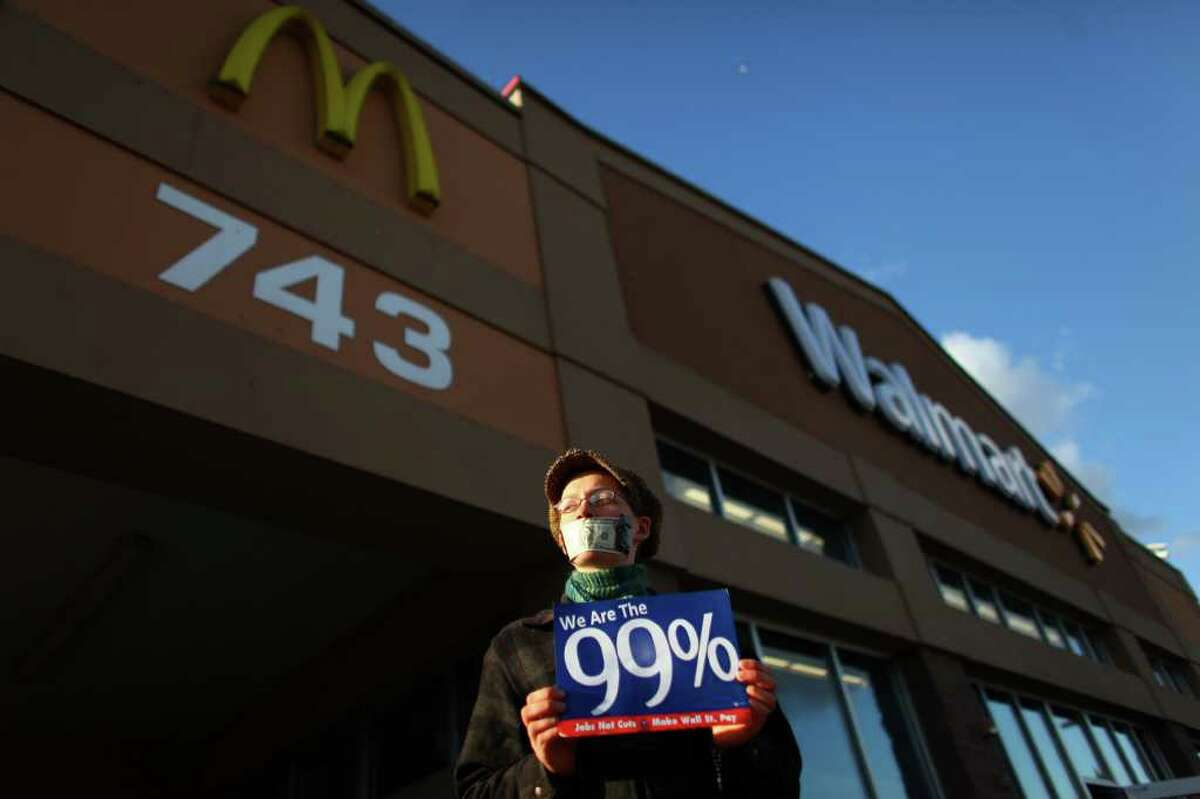 Lillian Kuehl holds a sign in front of Walmart in Renton during an Occupy Seattle protest at the retailer on Friday, November 25, 2011. A few dozen protesters gathered in front of the store and briefly marched through the store during the Black Friday protest.