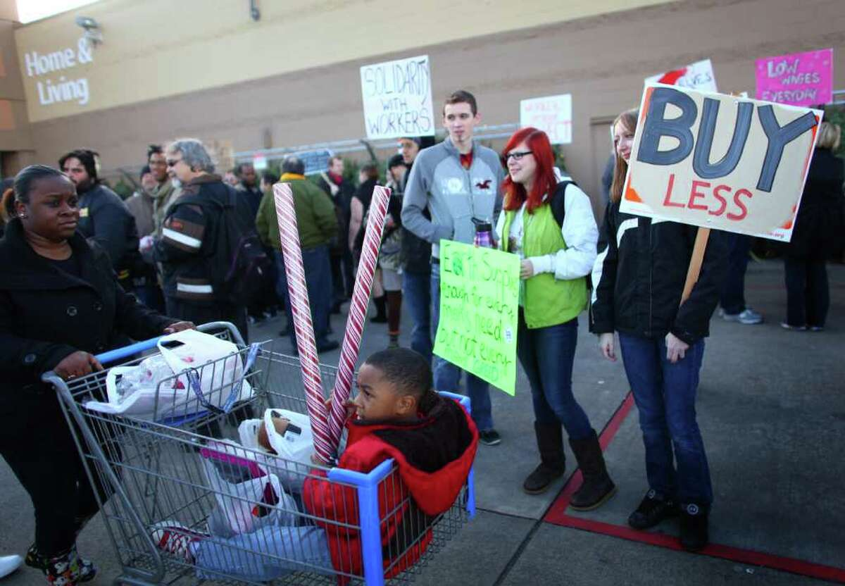 Protesters gather in front of Walmart in Renton during an Occupy Seattle protest as customers leave the retailer on Black Friday.