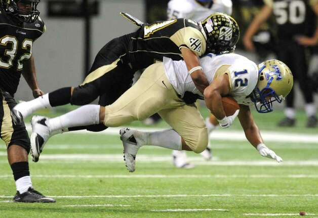 Kerville Tivy's Braedon White (12) is tackled by Jorge Torres of Port Lavaca Calhoun after catching a pass during Class 4A Region IV Division II regional playoff action at the Alamodome on Friday, Nov. 25 2011. BILLY CALZADA / gcalzada@express-news.net   Kerrville Tivy vs. Port Lavaca Calhoun Photo: BILLY CALZADA, Express-News / gcalzada@express-news.net