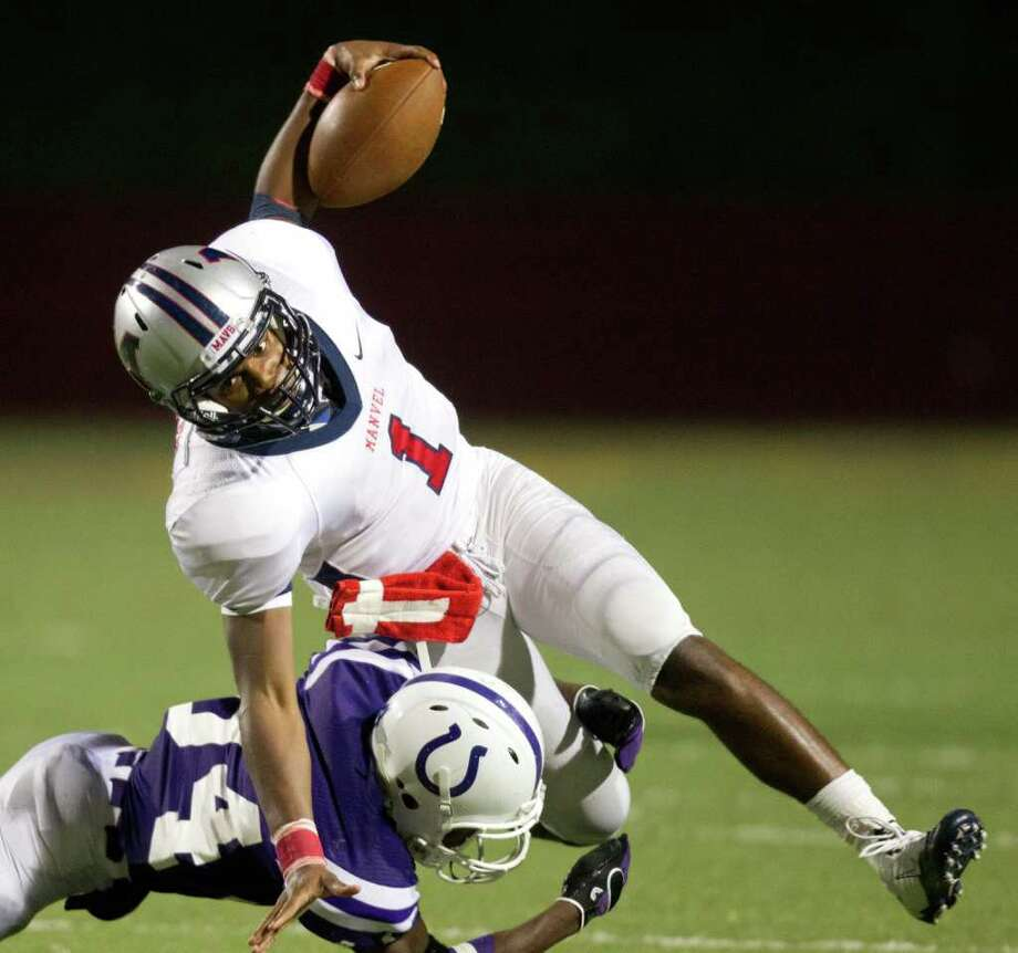 Manvel quarterback Julian Walker is upended by Dayton defender Rickey Shivers during the second half in Class 4A Div. II Region III semifinals high school playoff action at Abshier Stadium Friday, Nov. 25, 2011, in Deer Park. Manvel won the game 49-10. Photo: Smiley N. Pool, Houston Chronicle / © 2011  Houston Chronicle