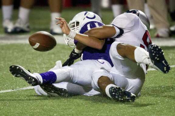 Dayton quarterback Andres Herrera (8) fumbles as he is dragged down by Manvel defensive end Glynn Cheeks (92) during the second half in Class 4A Div. II Region III semifinals high school playoff action at Abshier Stadium Friday, Nov. 25, 2011, in Deer Park. Manvel received the fumble and returned it for a touchdown and won the game 49-10.