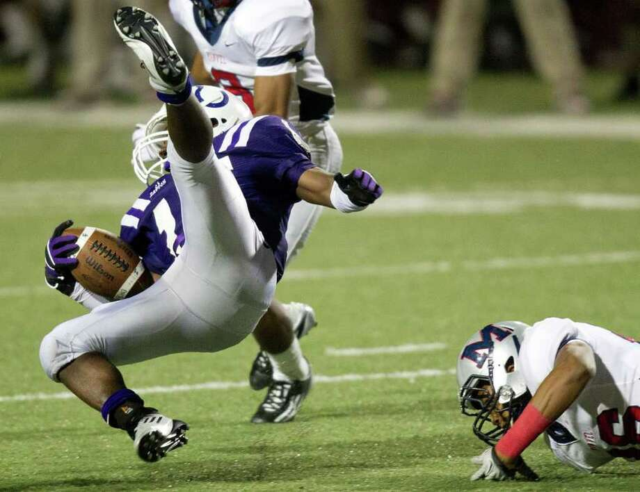 Dayton running back Ryan McBride (15)  is tripped up by Manvel linebacker  Chris Steib (26) during the second half in Class 4A Div. II Region III semifinals high school playoff action at Abshier Stadium Friday, Nov. 25, 2011, in Deer Park. Manvel won the game 49-10. Photo: Smiley N. Pool, Houston Chronicle / © 2011  Houston Chronicle