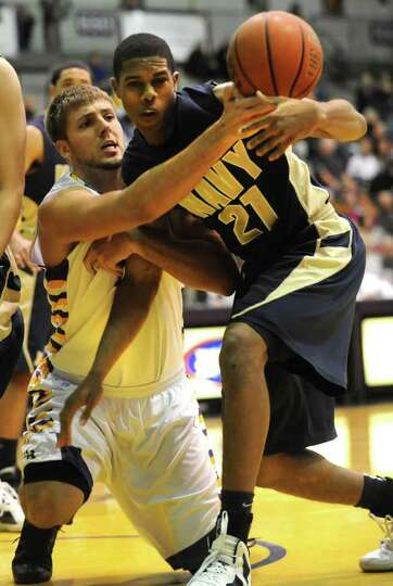 From left, Blake Metcalf of UAlbany battles for the rebound with Worth Smith of Navy during a basket