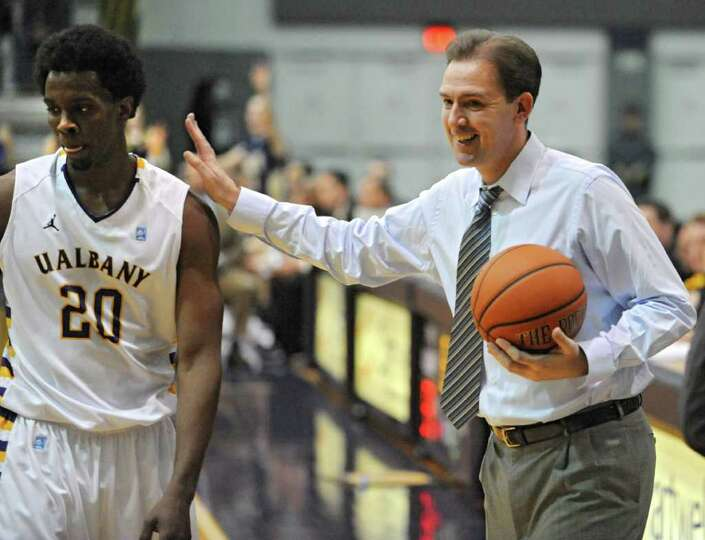 UAlbany coach Will Brown pats Gerardo Suero's shoulder during a basketball game against Navy at SEFC