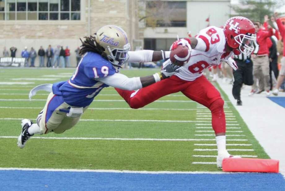 Nick de la Torre: Chronicle STRETCH PLAY: Patrick Edwards (83) found plenty of ways to get into the end zone Friday, scoring four touchdowns in the Cougars' 48-16 win over Tulsa that gave them the C-USA West title. Photo: Nick De La Torre / © 2011  Houston Chronicle