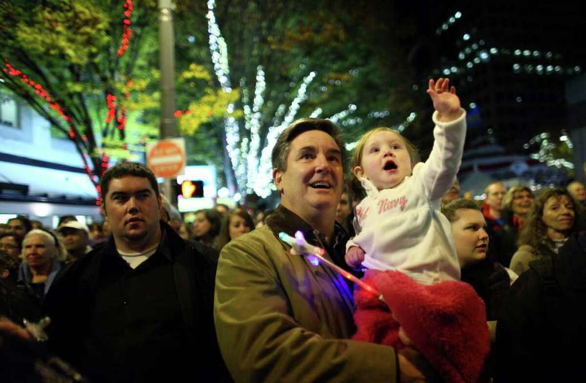 David Heric holds onto his grandaughter Payton Mulnis as Santa Claus makes an appearance during the Westlake Center Tree Lighting ceremony on Friday, November 25, 2011. Thousands of people packed into Westlake Park and surrounding streets for the annual holiday event.