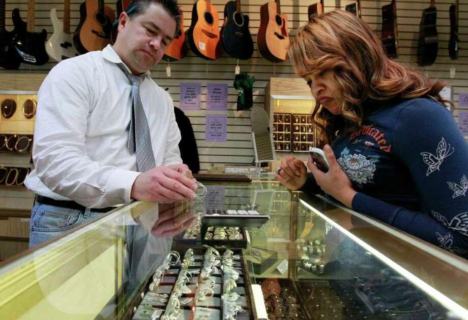 Steven Senne : ASSOCIATED PRESS DEALING: Loan officer Roy Knudsen of Boston displays earrings to Doreena Ruiz of Framingham, Mass., as Ruiz shops at Suffolk Jewelers & Pawnbrokers. Photo: Steven Senne / AP