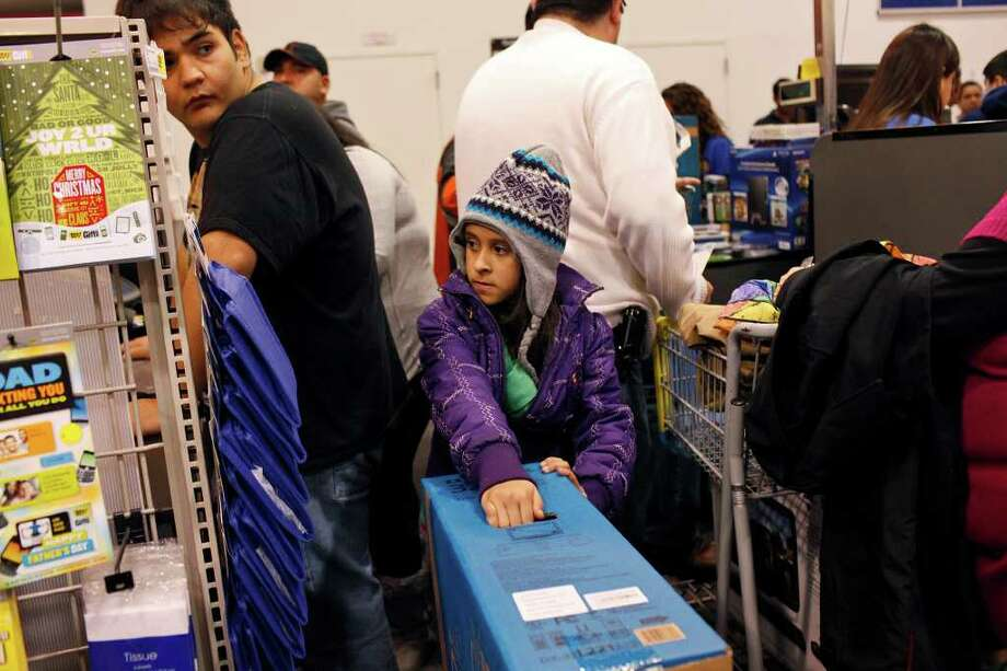Lenora Salas, 10, holds onto her family's television as she waits with her mother and sisters at the checkout line after the midnight opening at Best Buy in San Antonio on Friday, Nov. 25,  2011. Photo: LISA KRANTZ, SAN ANTONIO EXPRESS-NEWS  / SAN ANTONIO EXPRESS-NEWS
