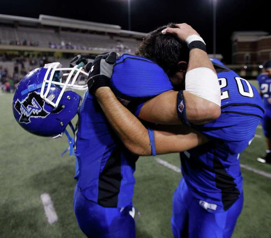 La Vernia's Aaron Grubb, left, and Zack Gonzalez (20) console one another after their loss to Columbia during the Class 3A Division 1 regional semifinals between Columbia and La Vernia November 25, 2011 at the Berry Center in Cypress, Texas. Columbia defeated La Vernia 28-7. Photo: Bob Levey, Houston Chronicle / ©2011 Bob Levey