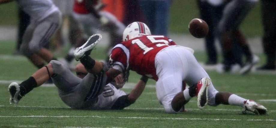 Pearland's Cody Sandman (left) fumbles the ball after being tackled by Lamar's Marvin Taylor during the first half of the 5A Division I Region III semifinal, Saturday, November 26, 2011 at Galena Park Stadium in Houston. Photo: Eric Christian Smith, For The Chronicle