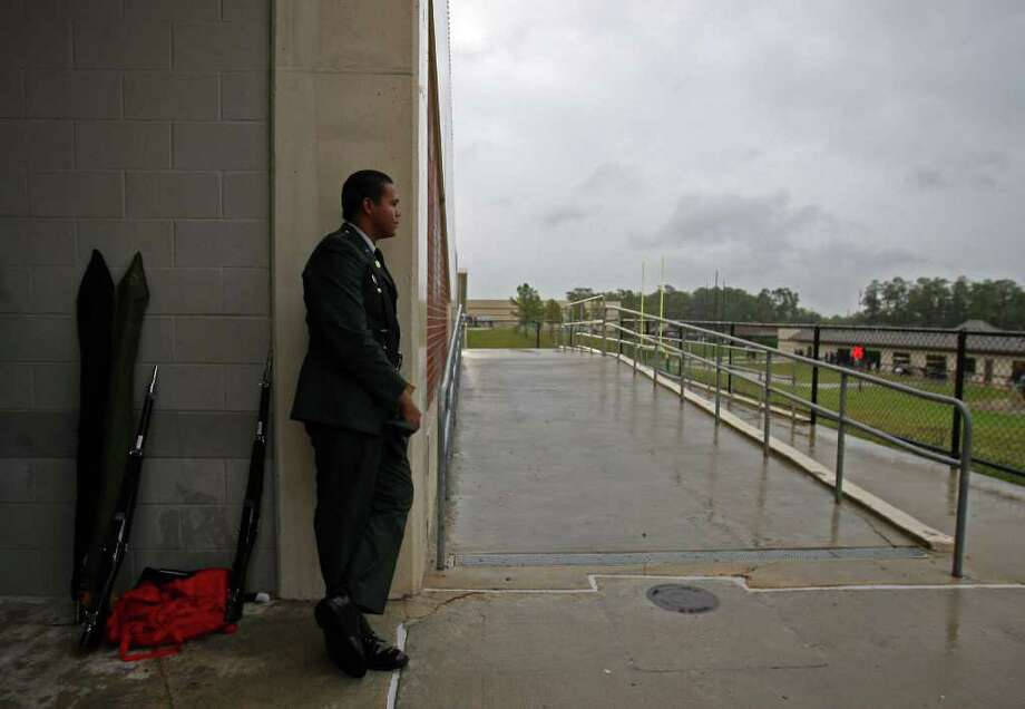 Lamar Junior ROTC member Rafael Mendez waits out a 35-minute lightning delay to the start of the 5A Division I Region III semifinal between the Lamar Redskins and the Pearland Oilers, Saturday, November 26, 2011 at Galena Park Stadium in Houston. Photo: Eric Christian Smith, For The Chronicle