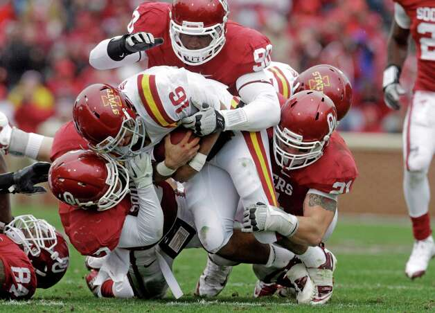 Iowa State quarterback Jared Barnett (16) is tackled by Oklahoma linebacker Corey Nelson (7), defensive end David King and linebacker Tom Wort in the first quarter of an NCAA college football game in Norman, Okla., Saturday, Nov. 26, 2011. Photo: Sue Ogrocki, Associated Press / AP