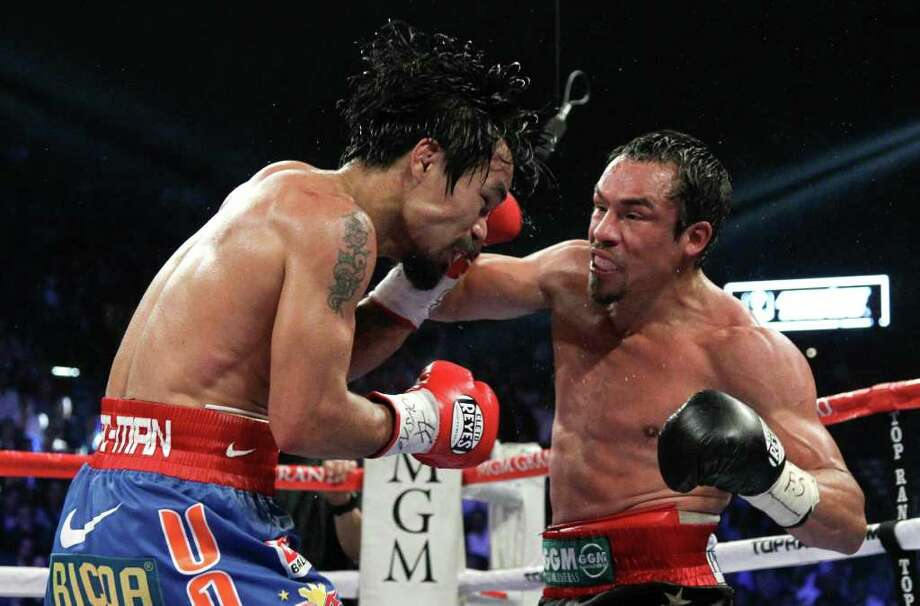 Manny Pacquiao (left) captured a narrow win over Juan Manuel Marquez in their WBO welterweight title bout. Photo: AP