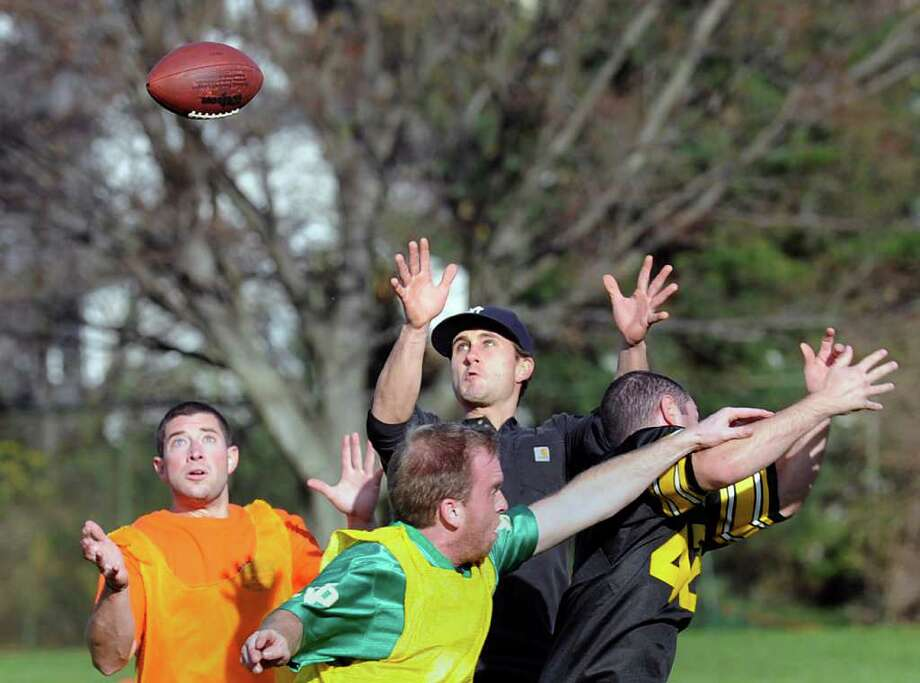 Receiver Damian Monick, wearing a cap, of the dark-shirted team, goes for the catch admid two defenders and a teammate during the 25th annual Turkey Bowl at Christiano Field in Chickahominy, Saturday afternoon, Nov. 26, 2011. Photo: Bob Luckey / Greenwich Time