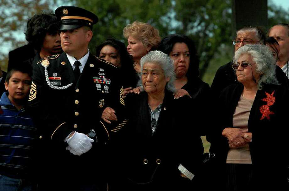 Sgt. Major Jesus Perez, from left, stands with Ruth G. Adams, the eldest sister of Pfc. Jimmie Jimenez Gaitan, 21, who died more than 60 years ago in a prison camp in North Korea and whose remains were recently identified, with Adams' daughter, Rebecca Hernandez, and another sister of Gaitan, Angie Gaitan, during his funeral at Fort Sam Houston National Cemetery in San Antonio on Saturday, Nov. 26, 2011. Photo: LISA KRANTZ, SAN ANTONIO EXPRESS-NEWS / SAN ANTONIO EXPRESS-NEWS