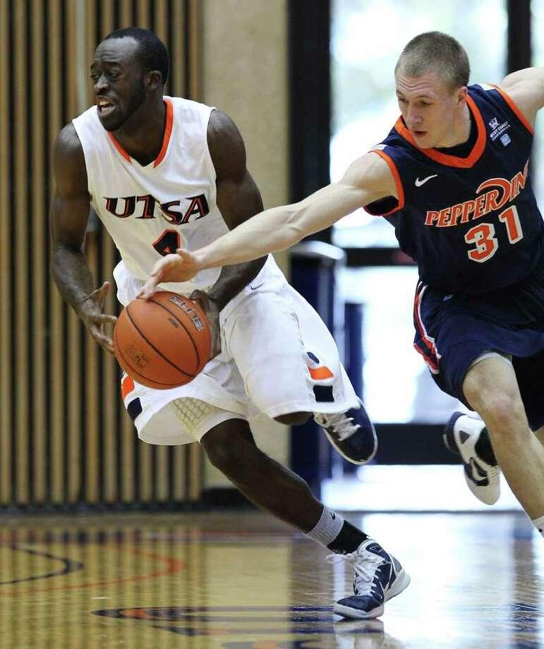 Pepperdine's Nikolas Skouen (31) goes for a steal against UTSA's Sei Paye (04) in men's college basketball at UTSA on Saturday, Nov. 26, 2011. UTSA loses to Pepperdine, 64-70, in overtime. Photo: KIN MAN HUI, ~ / SAN ANTONIO EXPRESS-NEWS