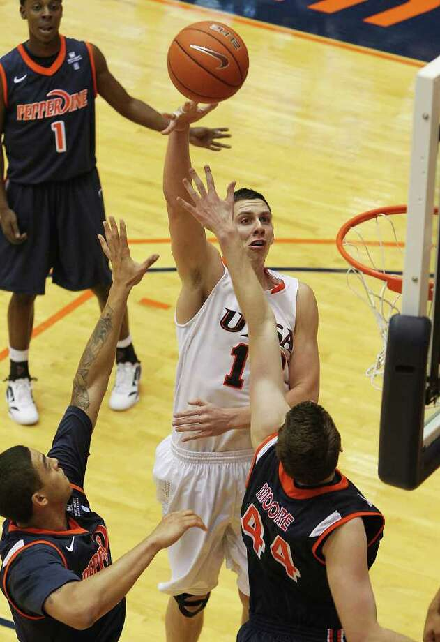 UTSA's Jeromie Hill (12) shoots over Pepperdine's Corbin Moore (44) and Taylor Darby (41) in men's college basketball at UTSA on Saturday, Nov. 26, 2011. UTSA loses to Pepperdine, 64-70, in overtime. Photo: KIN MAN HUI, ~ / SAN ANTONIO EXPRESS-NEWS
