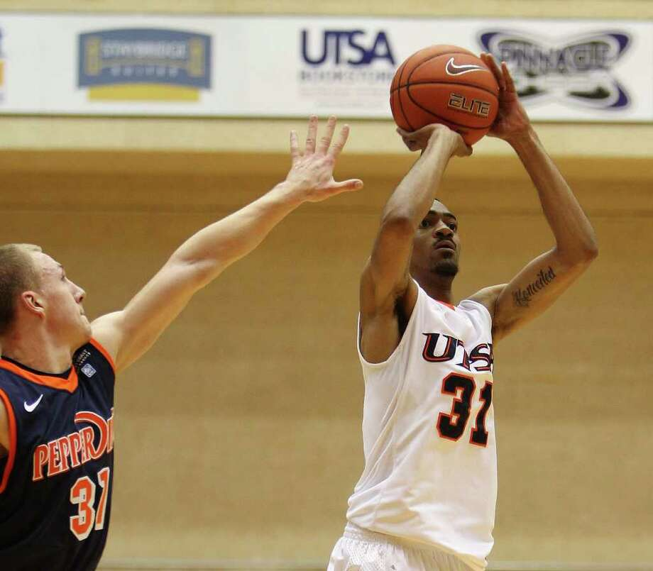UTSA's Melvin Johnson, III (31) attempts a shot against Pepperdine's Nikolas Skouen (left) in men's college basketball at UTSA on Saturday, Nov. 26, 2011. UTSA loses to Pepperdine, 64-70, in overtime. Photo: KIN MAN HUI, ~ / SAN ANTONIO EXPRESS-NEWS