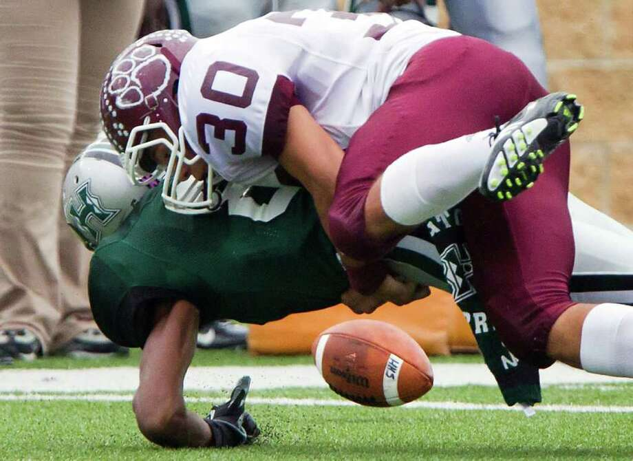 Hightower wide receiver Donald Weathersby (8) fumbles as he is hit by Cy-Fair defensive back Nathan Diamond (30) during the first half in Class 5A Div. I Region III semifinal high school playoff action at Tully Stadium on Saturday, Nov. 26, 2011, in Houston. Hightower recovered the fumble. Photo: Smiley N. Pool, Houston Chronicle / © 2011  Houston Chronicle