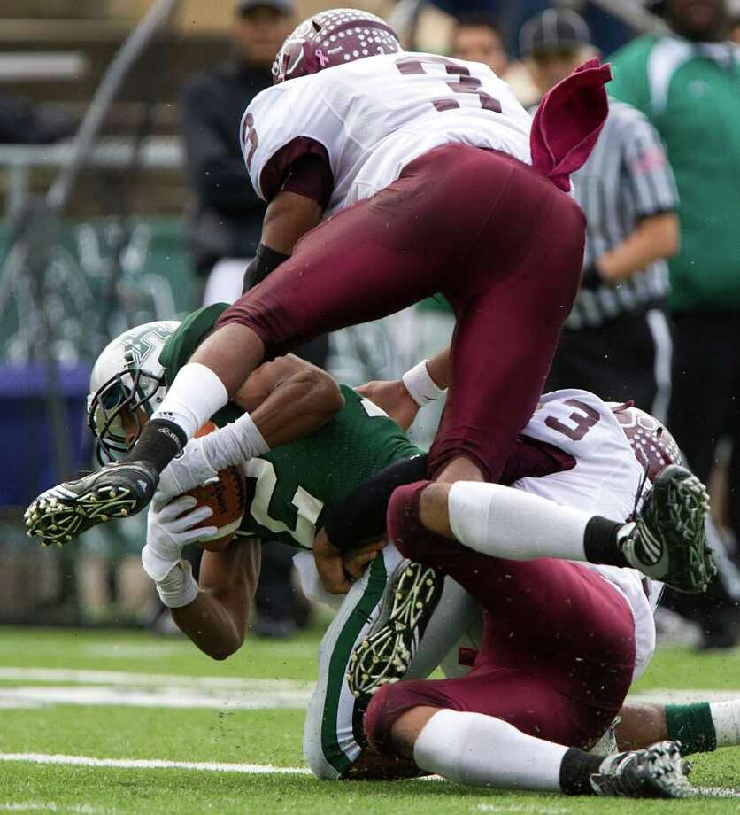 Hightower wide receiver Joseph Giles (12) is brought down by Cy-Fair defenders Dwight White (3) and Jalen Champagne (23) during the first half in Class 5A Div. I Region III semifinal high school playoff action at Tully Stadium, Saturday, Nov. 26, 2011, in Houston. Photo: Smiley N. Pool, Houston Chronicle / © 2011  Houston Chronicle