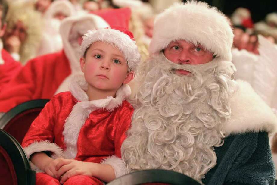Boris von Balnckenburg (L), 6, and his father Valentin von Balnckenburg join volunteer angels and Santas for their annual meeting at the Komoedie am Kurfuerstedamm theater. Photo: Sean Gallup, Getty / 2011 Getty Images