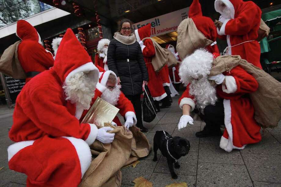 Volunteer Santas, who had just attended their annual meeting at the Komoedie am Kurfuerstedamm theater, greet a passerby and her dog outside on November 26, 2011 in Berlin, Germany. Photo: Sean Gallup, Getty / 2011 Getty Images