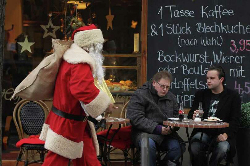 Two Swedish tourists look on as a volunteer Santa Claus, who had just attended the annual meeting of