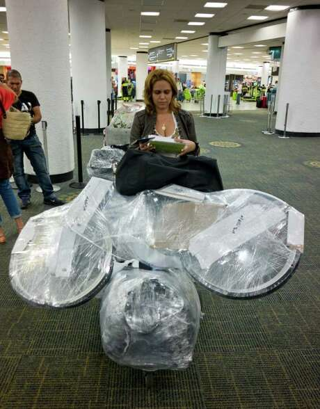 MAGGIE STEBER : NEW YORK TIMES CUBA-BOUND: Madelin Santiago of Hollywood, Fla., taking a bicycle and other gifts to her family in Cuba, waits for her flight at Miami International Airport. Photo: MAGGIE STEBER / NYTNS