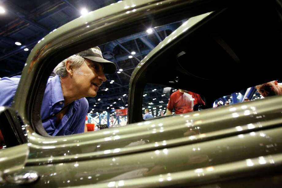 Em'ile Landry, left, and his son Brett Landry, right, of Pearland, get a close look at a 1933 Chevy during the  52nd Annual O'Reilly Auto Parts AutoRama at the George R. Brown Convention Center Saturday, Nov. 26, 2011, in Houston. Photo: Johnny Hanson, Houston Chronicle / © 2011 Houston Chronicle