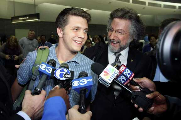 Gregory Porter, left, one of three U.S. students arrested during a demonstration in Cairo, and his attorney Theodore Simon, second from right, speak to members of the news media after arriving at Philadelphia International Airport, in Philadelphia, on Saturday Nov. 26, 2011, after an Egyptian court ordered the release of Porter and two other U.S. students who were arrested for throwing firebombs at security forces said Egyptian officials. (AP Photo/ Joseph Kaczmarek)