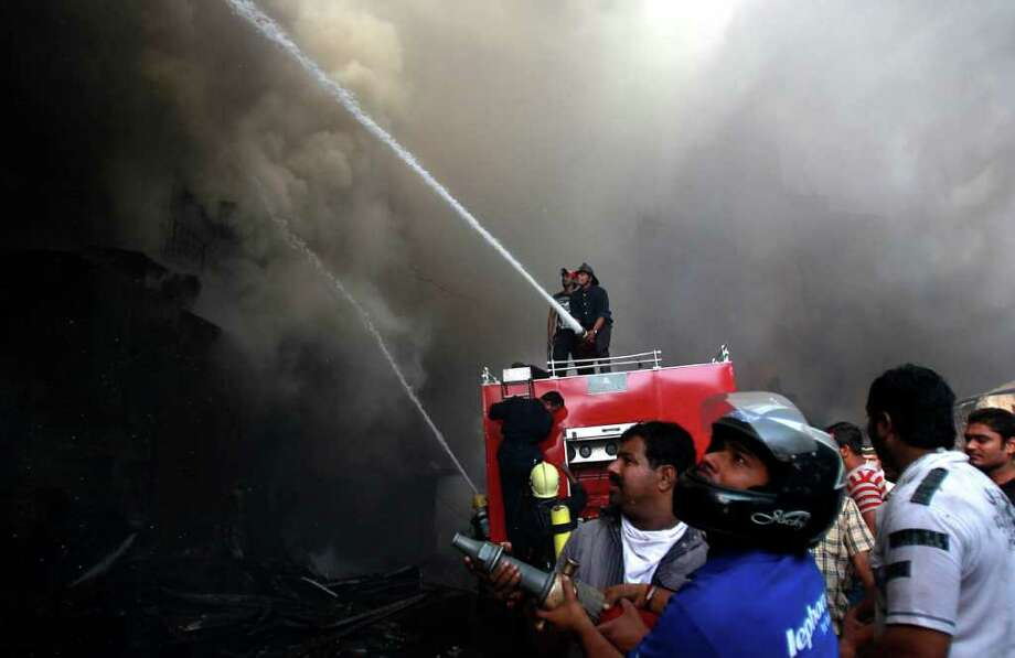Shopkeepers help firefighters extinguish a fire in Mumbai, India, Saturday, Nov. 26, 2011. A major fire engulfed a prominent commercial hub early Saturday leaving three firemen injured and gutting more than 300 shops, according to a news agency. Photo: Rafiq Maqbool, Associated Press / AP