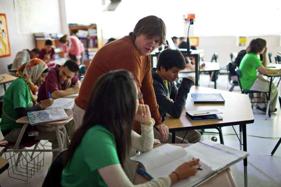 Cindy Fairbanks, one of HISD's new teacher development specialists, talks with a student while she also coaches and assesses history teacher Ashley Brown Bailey at Lee High School. Photo: Eric Kayne / © 2011 Eric Kayne