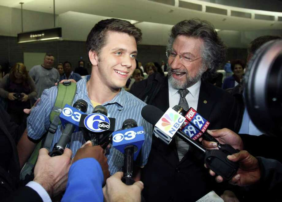 Gregory Porter, left, one of three U.S. students arrested during a demonstration in Cairo, and his attorney Theodore Simon, second from right, speak to members of the news media after arriving at Philadelphia International Airport, in Philadelphia, on Saturday Nov. 26, 2011, after an Egyptian court ordered the release of Porter and two other U.S. students who were arrested for throwing firebombs at security forces said Egyptian officials. (AP Photo/ Joseph Kaczmarek) Photo: Joseph Kaczmarek / FR109827 AP
