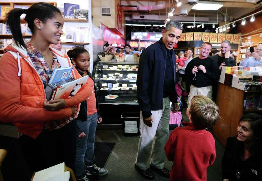 JEWEL SAMAD : AFP/GETTY IMAGES THINKING SMALL: President Barack Obama, with daughters Malia, left, and Sasha, second from left, speaks to a child at Kramerbooks and Afterwords in Washington. Saturday was the second annual Small Business Saturday, dedicated to supporting small retailers. Photo: JEWEL SAMAD / AFP