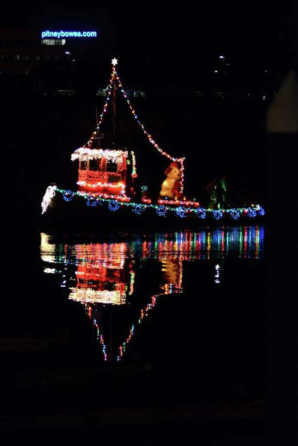 Lights on the David Steers tugboat reflect off of the water during the 6th annual Stamford Harbor Parade of Lights to benefit Toys for Tots and the Young Mariners Foundation at Harbor Point in Stamford on Saturday, Nov. 26, 2011. Steers, the owner of the boat, is a resident of Cos Cob. Photo: Amy Mortensen / Connecticut Post Freelance