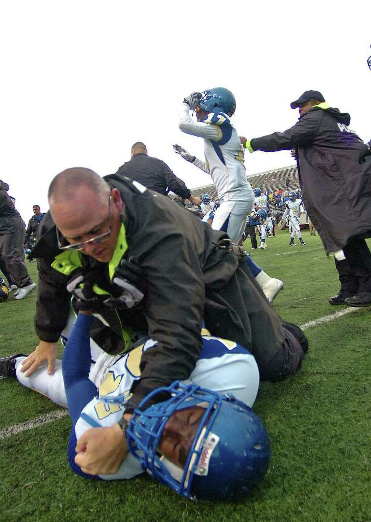 An Ozen player is pinned down by a security officer during a massive brawl following the Panther's game with La Marque at Stallworth Stadium on Saturday. The teams collided in the free-for-all shortly after shaking hands at the end of the game. The melee followed a smaller scuffle that occurred in the fourth quarter. Photo taken Saturday, November 26, 2011 Guiseppe Barranco/The Enterprise