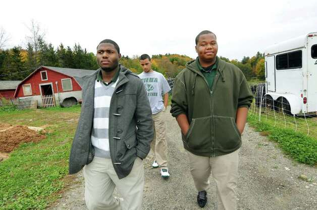 Khalid Cooper, 17, left, McKenna Fay, 18, center, and Ahsan Guy, 19, walks through the farm buildings on Wednesday, Oct. 12, 2011, at Berkshire Farm in Canaan, N.Y. (Cindy Schultz / Times Union) Photo: Cindy Schultz / 00014950A