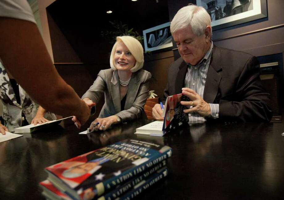 ERIK KELLAR : ASSOCIATED PRESS NEXT CHAPTER IN RACE: Republican presidential candidate Newt Gingrich signs a copy of his book Saturday as his wife, Callista, greets supporters during an event in Naples, Fla. Photo: Erik Kellar / FR170371 AP