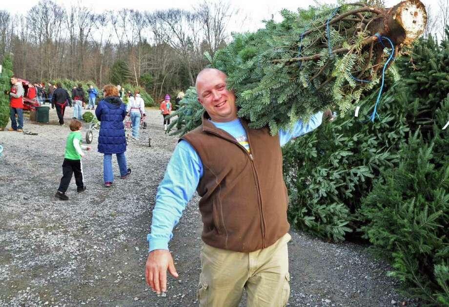 Sean Briscoe of Wilton carries a tree back to his car at the Ellms? Christmas Tree farm  in Charlton Saurday Nov. 26, 2011.   (John Carl D'Annibale / Times Union) Photo: John Carl D'Annibale / 00015520A