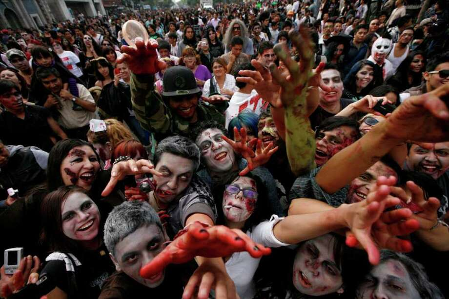 People dressed as zombies react to the camera during the V edition of the so-called 'Zombie Walk' in Mexico City, Saturday, Nov. 26, 2011. According to the organization 'Zombie Walk Mexico', the event gathered over 9,800 participants, breaking the previous record set in Asbury Park, in New Jersey in 2010 with 4,093 participants. Guinness World Records have not officially confirmed if Mexico holds the new record. Photo: AP