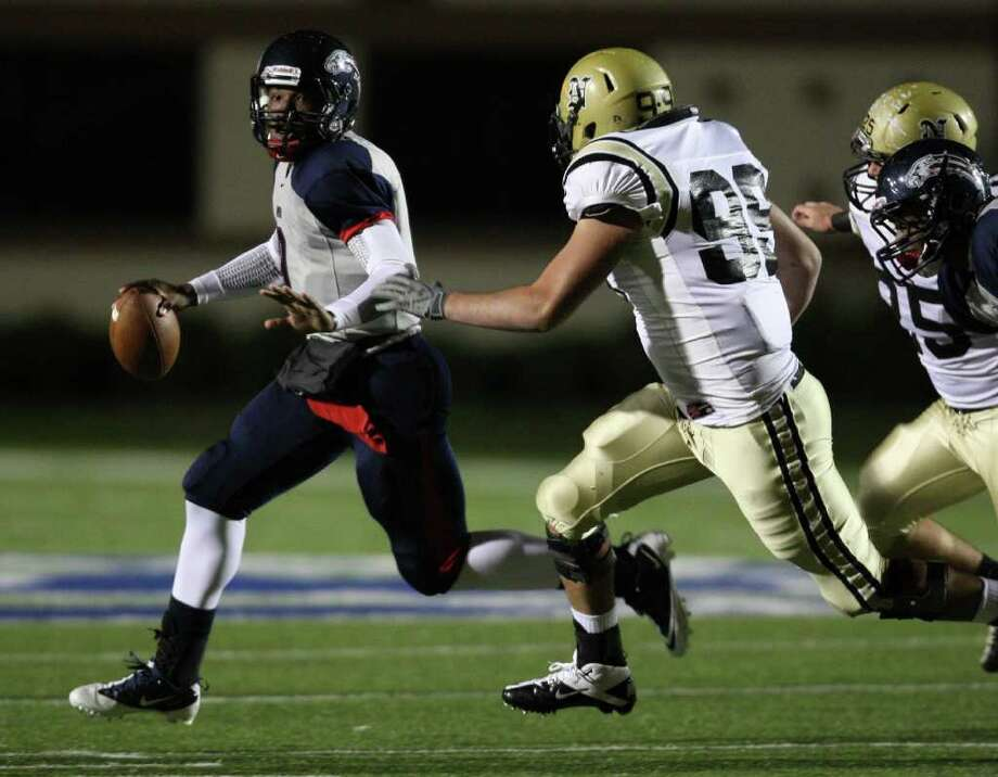 Dawson quarterback Garry Kimble (left) looks for an open receiver as Nederland defender Corbin Carr closes in during the first half of the 4A Division I Region III semifinal, Saturday, November 26, 2011 at Galena Park Stadium in Houston. Photo: Eric Christian Smith, For The Chronicle