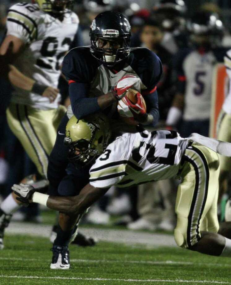 Dawson's Tony Upchurch (left) is tackled by Nederland's Korey Hopkins during the first half of the 4A Division I Region III semifinal, Saturday, November 26, 2011 at Galena Park Stadium in Houston. Photo: Eric Christian Smith, For The Chronicle