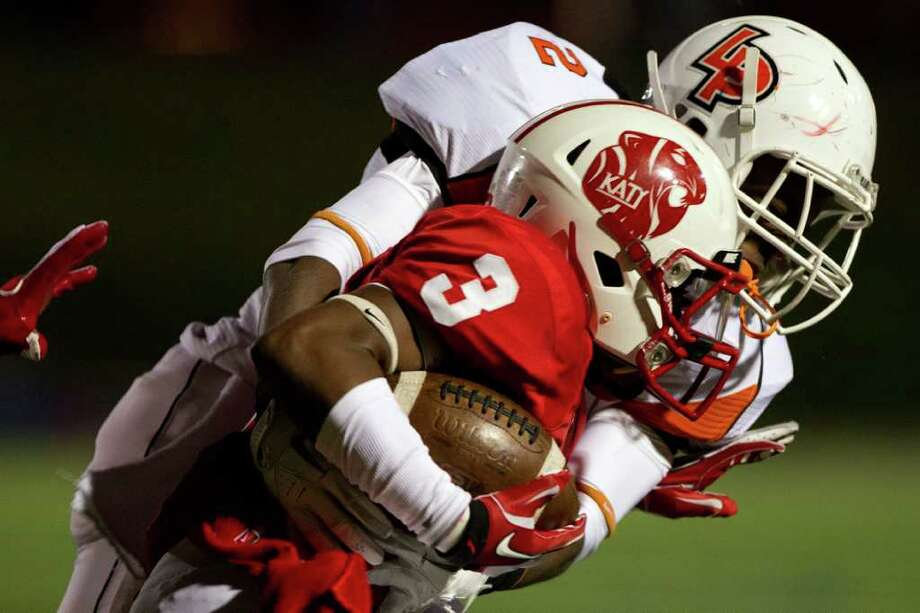 Katy wide receiver Jordan Thompson (3) is brought down by La Porte defensive back Ellis Hutchinson (2) during the first half in Class 5A Div. II Region III semifinal high school playoff action at Tully Stadium Saturday, Nov. 26, 2011, in Houston. Photo: Smiley N. Pool, Houston Chronicle / © 2011  Houston Chronicle