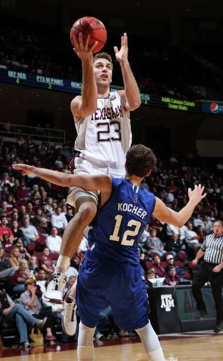 JON EILTS: ASSOCIATED PRESS UP AND OVER: Texas A&M-Corpus Christi's Jake Kocher stands his ground as Texas A&M's Zach Kinsley drives in for a shot during the first half of Saturday's game at College Station. Photo: Jon Eilts / FR170396 AP