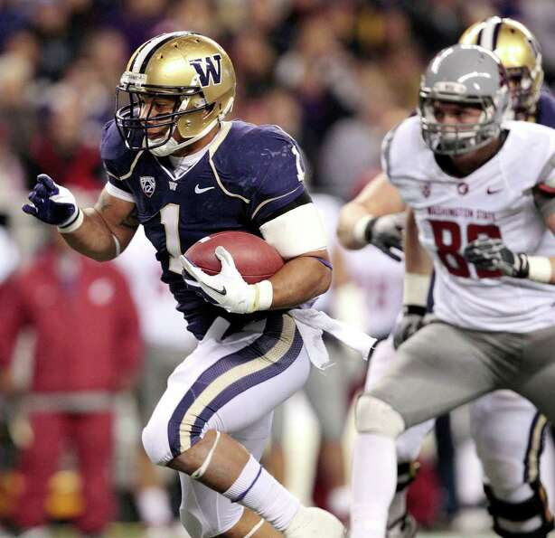 Washington's Chris Polk, left, runs against Washington State in the first half of an NCAA college fo