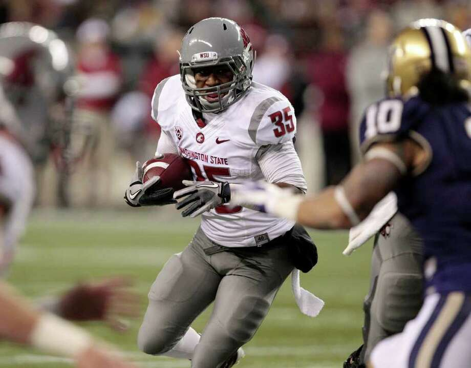 Washington State's Marcus Mason (35) runs against Washington in the first half of an NCAA football game on Saturday, Nov. 26, 2011, in Seattle. Photo: AP