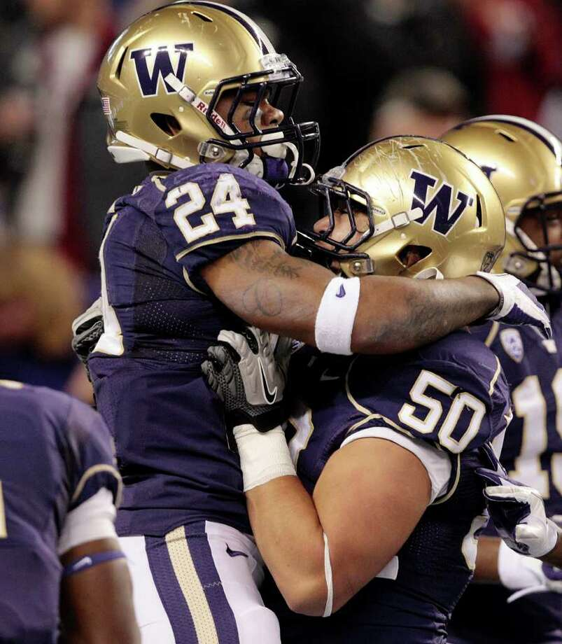 Washington's Jesse Callier (24) celebrates with Thomas Tutogi after scoring on a blocked punt against Washington State in the first half of an NCAA college football game on Saturday, Nov. 26, 2011, in Seattle. Photo: AP