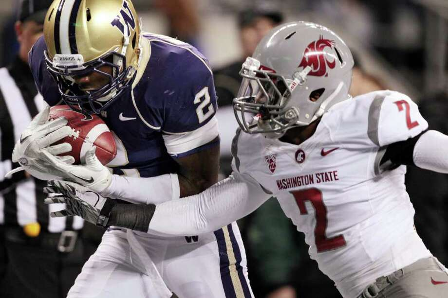 Washington's Kasen Williams, left, hauls in a 16-yard touchdown reception in front of Washington State's Nolan Washington in the first half of an NCAA college football game on Saturday, Nov. 26, 2011, in Seattle. Photo: AP