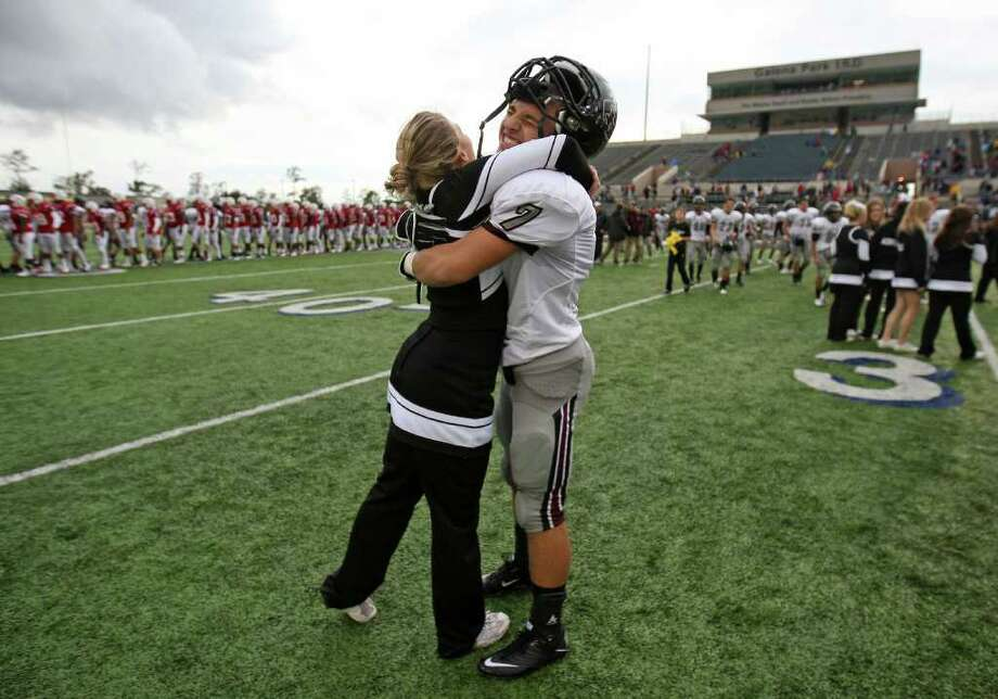 Pearland's Cody Rost (7) hugs cheerleader Nikki Eatadower after the Oilers' 35-14 victory over the Lamar Redskins in the 5A Division I Region III semifinal, Saturday, November 26, 2011 at Galena Park Stadium in Houston. Photo: Eric Christian Smith, For The Chronicle
