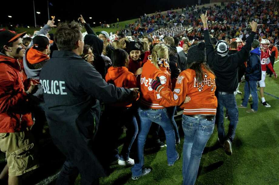 Police officers try to clear La Porte fans from the field after the Bulldogs defeated Katy 9-7 in Class 5A Div. II Region III semifinal high school playoff action at Tully Stadium, Saturday, Nov. 26, 2011, in Houston. Photo: Smiley N. Pool, Houston Chronicle / © 2011  Houston Chronicle